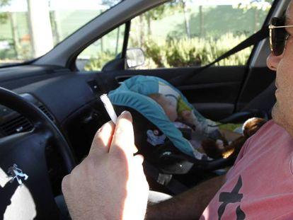 Un conductor fuma en el coche con un bebé al lado.