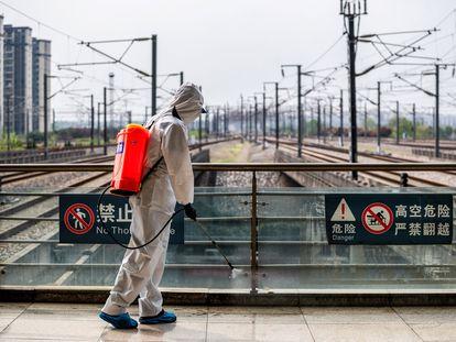 Un trabajador desinfecta la estación de tren de Wuhan, en marzo.