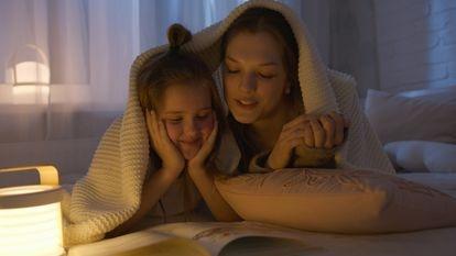 Una madre lee con su hija en la cama.