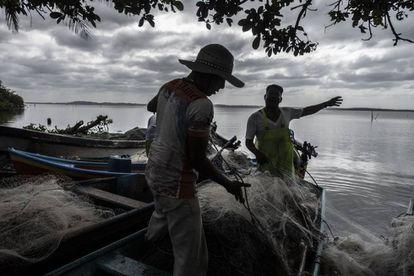 Pescadores trabajan en la laguna en los alrededores del sitio acordonado donde se ubican las excavaciones.