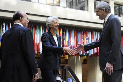 Christine Lagarde saluda al director en funciones del FMI, John Lipsky, en presencia de Shakour Shaalan, miembro del comité ejecutivo, ayer en la sede de la institución, en Washington.