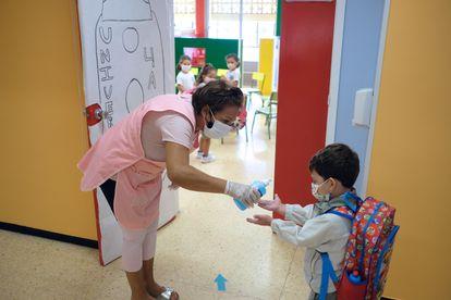 Una profesora echa gel hidroalcohólico en manos de un niño antes de entrar a su clase en Canarias.