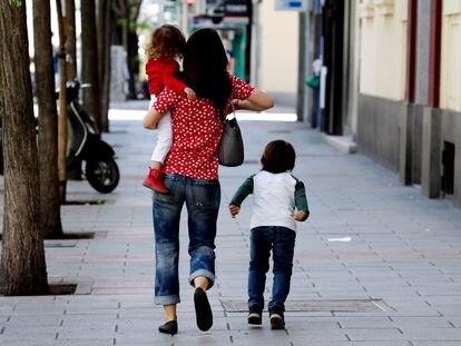 Dos niños acompañados de un adulto por el centro de Madrid durante la pandemia de coronavirus.