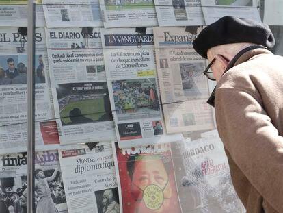 Un hombre observa los diarios con noticias sobre el coronavirus en un kiosko de periódicos de San Sebastián.