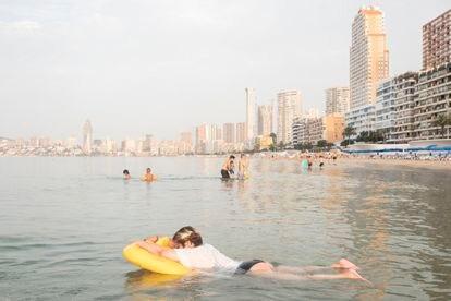 Miluzka Arias, organizadora del Bus Playero Viajero, descansa sobre un flotador en la playa de Benidorm durante el amanecer del sábado.