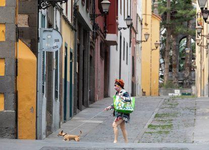 Una mujer con mascarilla pasea a su perro en Las Palmas de Gran Canaria.