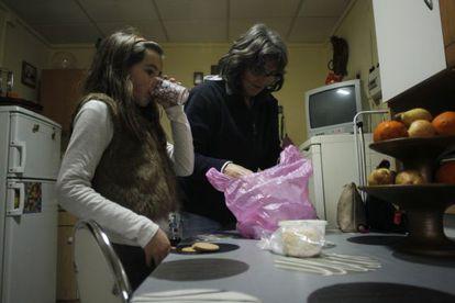 La niña portuguesa Matilde Alexandra Alves bebe un vaso de leche mientras su madre Maria Alexandra Gomez saca de la bolsa la comida dada por el ayuntamiento de Elvas (Portugal).