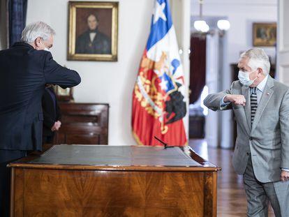 El presidente de Chile, Sebastián Piñera (izquierda), saluda a la distancia a su nuevo ministro de Salud, Enrique París (derecha).