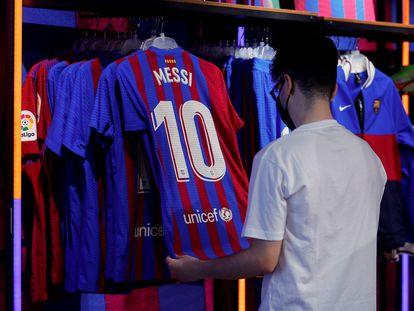 Un aficionado mira una camiseta de Messi en una tienda de Barcelona.