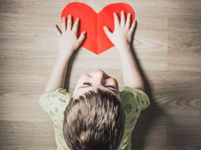 Un niño sujeta un corazón de papel.