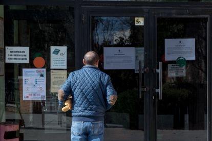 Una persona lee un cartel en el centro municipal de mayores de Valdemoro al que asistía un jubilado contagiado por coronavirus fallecido este jueves.