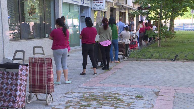Cola de personas esperando a recibir alimentos y productos de primera necesidad en Madrid.