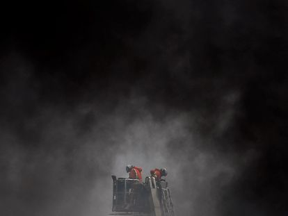 Dos bomberos trabajan este miércoles en el control y extinción del incendio declarado en una nave industrial de Aldaia (Valencia).