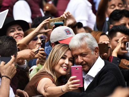 Una mujer se toma una selfi con López Obrador.