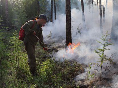 Un bombero trata de sofocar unas llamas en una zona forestal de la región de Yakutia (Rusia) el pasado miércoles.