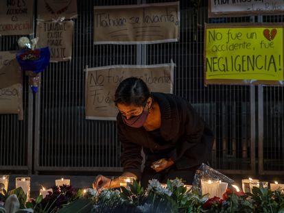 Una mujer coloca una vez y flores durante una velada en protesta donde ocurrió el accidente de la linea 12 del metro en Ciudad de México