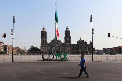 Un hombre camina por un costado de la desolada explanada del Zócalo.