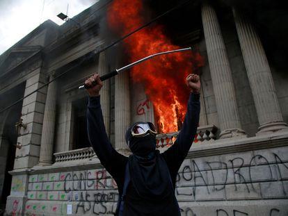 Un hombre protesta en frente del Congreso de Guatemala en llamas. En video, imágenes de las protestas.