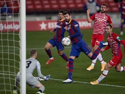 El defensa del Barcelona Gerard Piqué remata un balón ante el portero Aarón Escandell, del Granada.