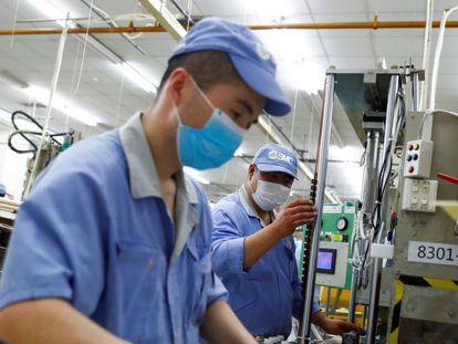 Empleados chinos en una fábrica china de componentes.