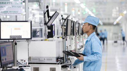 Un empleado revisa el proceso de producción de los smartphones.