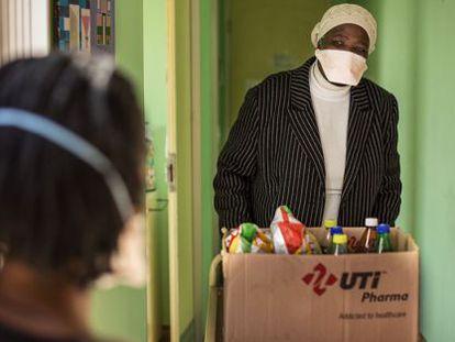 Una enfermera de la clínica Lizo Nobanda en Ciudad del Cabo lleva comida a enfermos de tuberculosis.