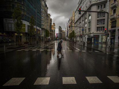 Una mujer cruza un paso de peatones en la Gran Vía de Madrid durante el confinamiento, el pasado marzo.