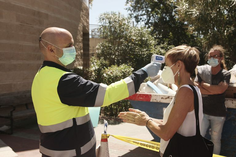 Un sanitario le toma la temperatura a una mujer que espera para hacerse una PCR en Madrid (España), el pasado sábado.