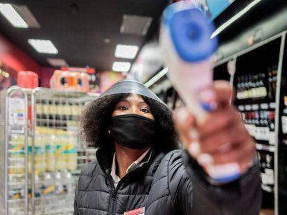 Una empleada de una licorería de Johanesburgo (Sudáfrica) toma la temperatura a los clientes que acceden al local el pasado 18 de agosto, el mismo día en que el Gobierno levantó la prohibición de vender alcohol y tabaco como medida para prevenir la propagación de la covid-19.