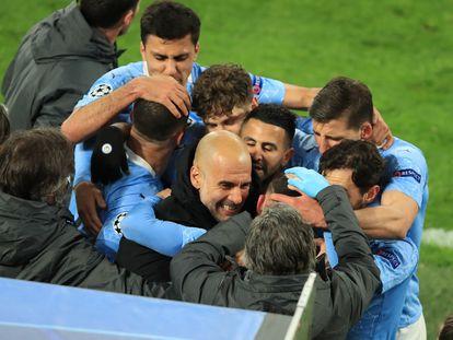 Los jugadores del City abrazan a Guardiola tras un gol