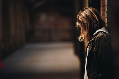 Una chica triste está sola en una calle.