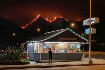 Un hombre en un restaurante mientras al fondo se ven las llamas que devoraban el jueves por la noche las colinas del Parque Nacional de Los Ángeles.