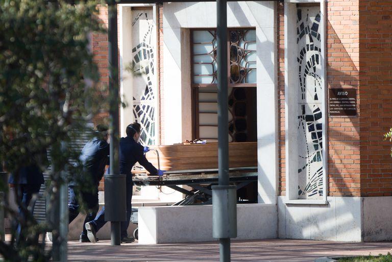 Dos trabajadores introducen un ataúd por la puerta de la funeraria municipal de Madrid el 25 de marzo