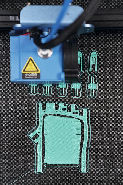 Una impresora 3D fabrica la primera capa de una palma y unos dedos para un pedido de mano derecha para un niño.