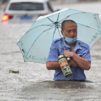 This photo taken on July 20, 2021 shows a man wading through flood waters along a street following heavy rains in Zhengzhou in China's central Henan province. (Photo by STR / AFP) / China OUT
