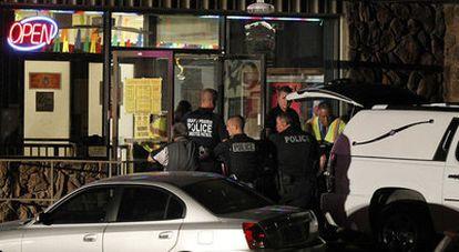 Policías en la puerta del local donde se produjo el tiroteo en el que murieron seis personas.