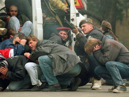 Un soldado bosnio entre varios civiles dispara hacia un francotirador serbio, en el centro de Sarajevo el 6 de abril de 1992.