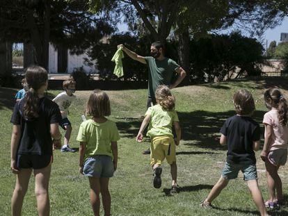 Niños jugando con su monitor en un campamento de verano en la provincia de Barcelona, este lunes.