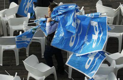 Un niño recoge los banderines del PP tras el mitin de Rajoy en Sevilla.