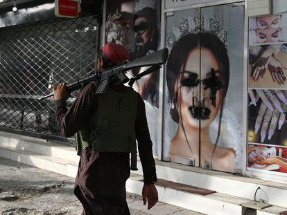 Un guerrillero talibán pasa delante de un salón de belleza en Kabul donde las imágenes de las mujeres se han censurado con aerosol negro, este miércoles.