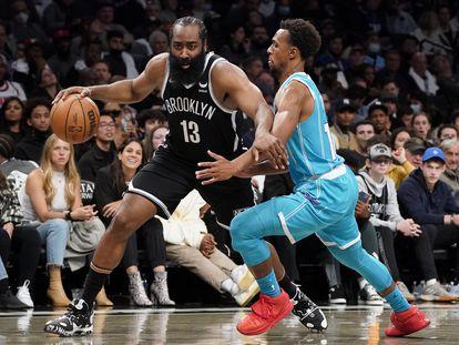 Harden aparta a Ish con su brazo izquierdo durante el partido entre Brooklyn y Charlotte.