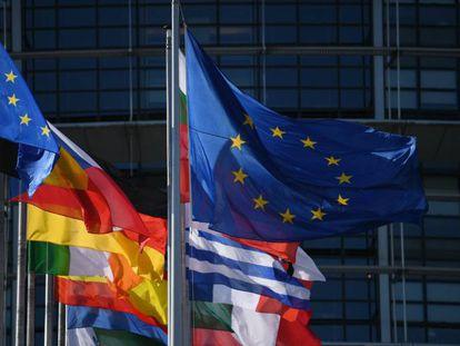 Vista exterior del Parlamento Europeo que muestra las banderas de los países miembro de la Unión Europea.