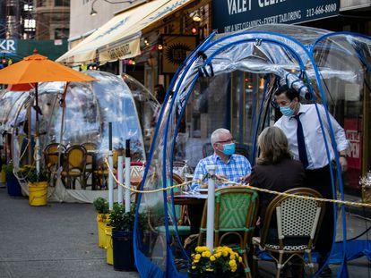 Clientes de una cafetería de Nueva York, protegidos por una burbuja de plástico.