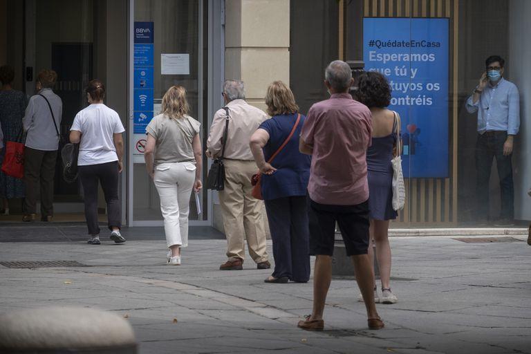 Varias personas esperan su turno en la calle para entrar en un banco en Sevilla, este lunes.
