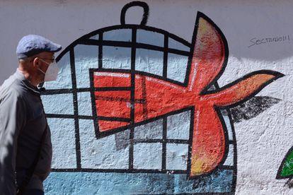 Un hombre pasa por delante de un mural que representa la salida de la jaula de un pájaro, este domingo en Valladolid.