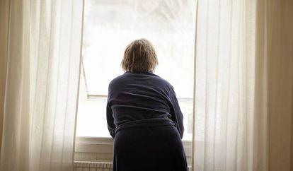 Una mujer asomada a una ventana, en una imagen de archivo.