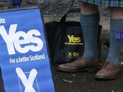 Un hombre a favor de la independencia de Escocia, junto a un cartel a favor del sí.