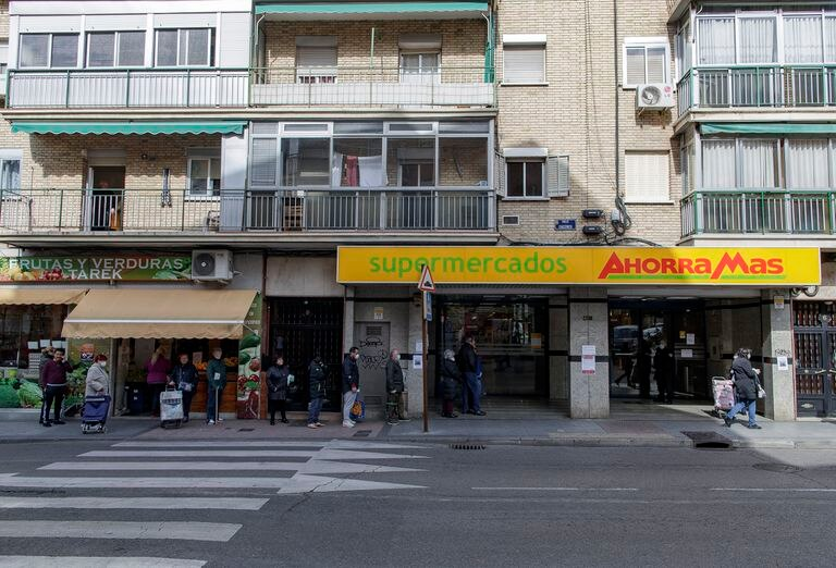 Varias personas con mascarilla hacen cola en un supermercado Ahorra Más a primera hora de la mañana, en Alcorcón.