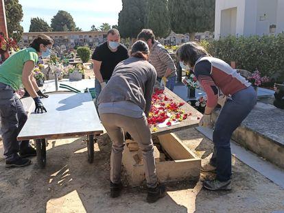 Un grupo de personas levanta una lápida en el cementerio de Paterna (Valencia), el pasado 21 de abril.