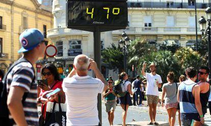 Viandantes fotografían un termómetro en el centro de Valencia, este martes.